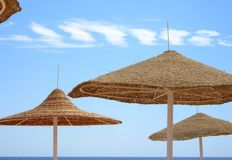 Beach Umbrellas. In front of Blue Sky and White Cloud Stock Photo