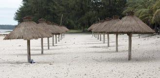 Beach Umbrellas. Row of grass beach umbreallas on a white beach in Mozambique Royalty Free Stock Photos