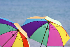 Beach umbrellas. A pair of colorful beach umbrellas with lake in background Stock Photography