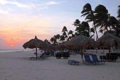 Beach umbrellas and beach chairs on Manchebo beach on Aruba. Island at sunset Royalty Free Stock Photos