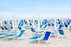 Beach umbrellas and blue deckchairs Royalty Free Stock Photos