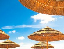 Beach umbrellas on blue sky background with clouds Stock Photos