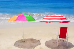 Beach umbrellas and chair by the ocean Royalty Free Stock Images