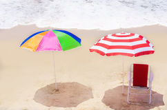 Beach umbrellas and chair by the ocean Royalty Free Stock Image