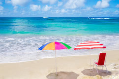 Beach umbrellas and chair by the ocean Royalty Free Stock Photos