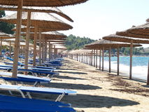 Beach umbrellas and chairs. A view looking down several rows of thatched beach umbrellas and lounge chairs on a sandy beach at a resort Royalty Free Stock Photo