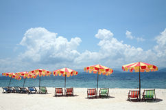 Beach umbrellas and chairs. Beach umbrellas and deck chairs on the beach with a beautiful sky Stock Images
