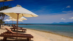 Beach umbrellas chairs on gold sand against azure sea. View of beach umbrellas and beach chairs on gold sand against azure sea distant islands stock video footage
