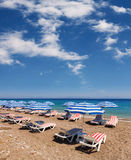 Beach with Umbrellas and Chairs under the sun and  blue sky Royalty Free Stock Images