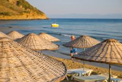 Beach umbrellas and chaise lounges with sea and sky in the background.  royalty free stock image