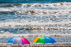 Beach Umbrellas and Crashing Ocean Waves. Vivid seascape of two colorful beach umbrellas facing a beautiful sea of crashing waves.  Horizontal. Copy space Stock Image