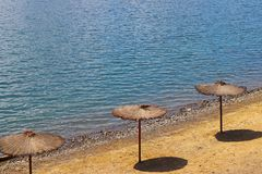 Beach with umbrellas from a creeper. Quality and comfort of rest at the water. Protection from sunlight. Rest on the beach and pon stock photo