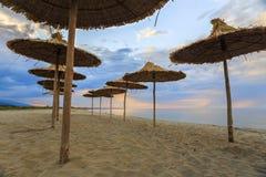 Beach with umbrellas. Dawn at deserted beach with umbrellas Stock Photos