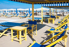 Beach umbrellas, deck chairs, tents on sand by sea Royalty Free Stock Photos