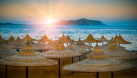 Beach umbrellas. Egypt summer shore at sunset. Royalty Free Stock Photos