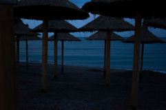 Beach umbrellas on an empty beach at dusk Royalty Free Stock Images