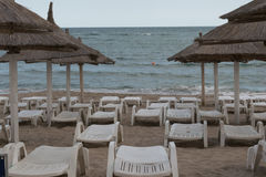 Beach umbrellas, empty sunbeds and lounge chairs at the beach in the romanian seaside in Neptun, Constanta Romania Stock Image