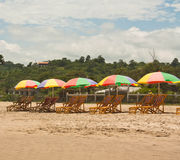 Beach Umbrellas. Lounge chairs and colorful beach umbrellas line the sandy beach in Montanita Ecuador South America on a sunny day Stock Photography