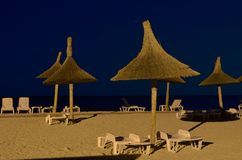 Beach umbrellas, lounge chairs, night Stock Image