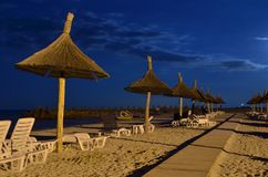 Beach umbrellas, lounge chairs, night Stock Photography