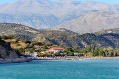 Beach with umbrellas among mountains near Aghia Galini town at Crete island Royalty Free Stock Photo
