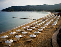 Beach and umbrellas. Beach panorama with lots of umbrellas at the isle of Elba, Italy. Photo taken in the morning royalty free stock photos