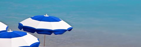 Beach umbrellas, panoramic blue ocean background royalty free stock photo