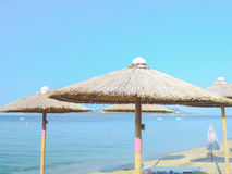 Beach umbrellas. Parasols with beautiful hats on top Royalty Free Stock Photo