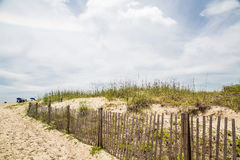 Beach Umbrellas Past Fence and Sand Dunes Royalty Free Stock Photo