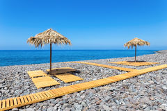 Beach umbrellas with path and stones at portuguese sea Royalty Free Stock Image