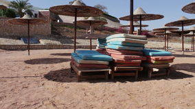 Beach umbrellas in Red Sea. Many Parasols and beach mattresses on the empty beach of the Red Sea stock footage