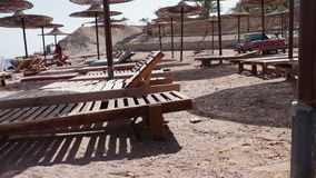 Beach umbrellas in Red Sea. Many Parasols and beach mattresses on the empty beach of the Red Sea stock video