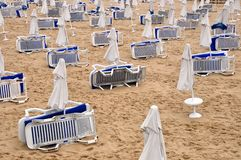 Beach umbrellas in rows. Beach umbrellas and deck chairs in rows off season Royalty Free Stock Photography
