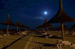 Beach umbrellas, sidewalk, full moon stock photo