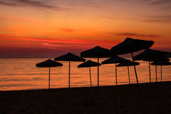 Beach umbrellas silhouettes at dawn Stock Images