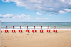 A beach with umbrellas and sun beds on coast Royalty Free Stock Images