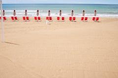 A beach with umbrellas and sun beds on coast Stock Photos
