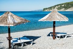 Beach umbrellas and sun beds on the ocean royalty free stock images