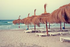 Beach with umbrellas and sun beds before storm royalty free stock images