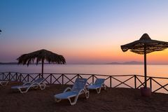 Beach umbrellas and sun lounger  at sunrise Royalty Free Stock Photography