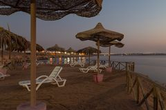 Beach umbrellas and sun loungers on the beach at dusk . Red sea. Stock Photography