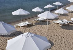 Beach umbrellas and sun loungers. Parasols and sun loungers in white on the beach stock photography