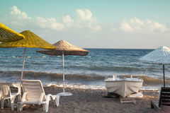 Beach with umbrellas and sun loungers. Small boat on the shore. Royalty Free Stock Photography