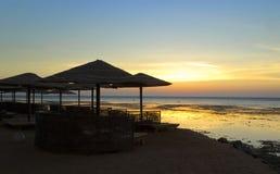 Beach umbrellas and sunbeds on the beach. Morning seascape Royalty Free Stock Photos
