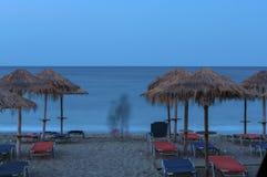 Beach Umbrellas in sunset. Beach Umbrellas, sunset in Pelion, Greece Royalty Free Stock Photography