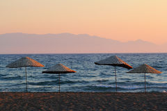 Beach umbrellas at sunset Stock Photos