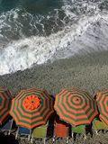 Beach Umbrellas. A view of beach umbrellas and chairs on a rocky beach close to the advancing tide Stock Image