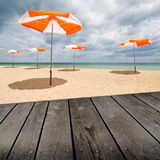 Beach umbrellas on the white sand and empty wooden deck table. Royalty Free Stock Photo