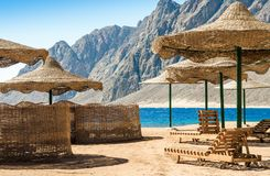 Beach umbrellas and wooden lounge chairs on the sand of the beach against the backdrop of the sea and high rocky mountains in stock photos