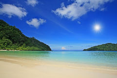 Beach under blue cloudy sky and sun beam Royalty Free Stock Photography